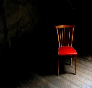 Empty chair in a dark room